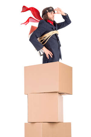 Businessman with homemade rocket and googles on top off a stack of cardboard boxes, ready to take off