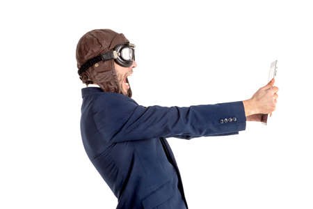 Businessman with pilot goggles and tablet isolated in white