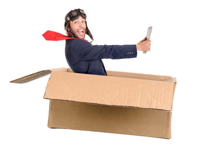 Businessman with tablet flying a carboard box isolated in white