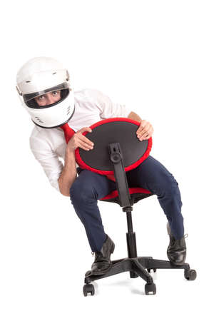 Businessman racing in an office chair with helmet, isolated in white