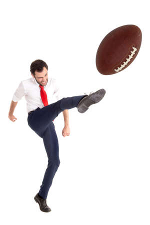 Businessman kicking  aa American football ball or rugby ball isolated in white