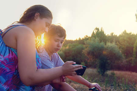 Young woman showing a video or photo in the phone to a boy in a bicycle at sunset outdoors