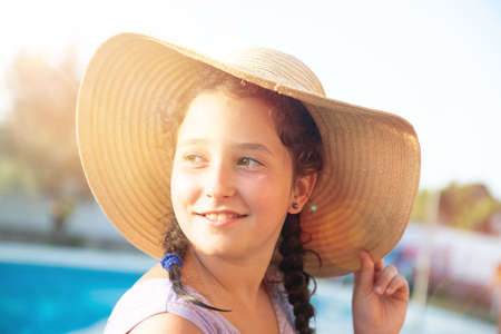 Sweet young girl posing with hat outdoors at sunset