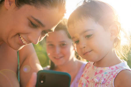 Girls looking at a phone outdoors at sunset