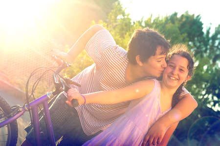 Young boy kissing a girl outdoors at sunset, near a bicycle Zdjęcie Seryjne