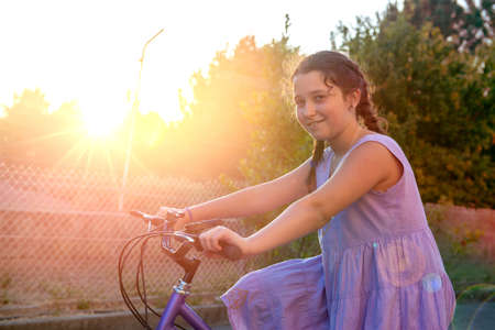 Happy young girl posing in a bicycle outdoors at sunset