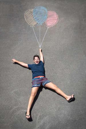 Young boy playing with chalk drawn balloons Zdjęcie Seryjne