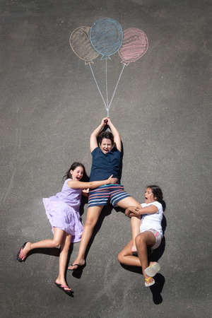 Young kids playing with chalk drawn balloons