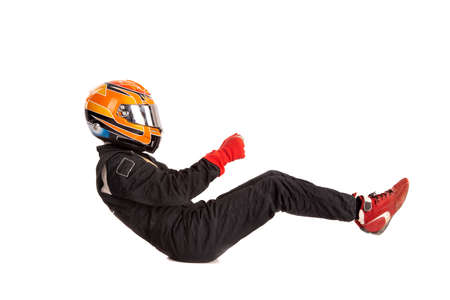 Racing driver in racing position with complete gear isolated in white
