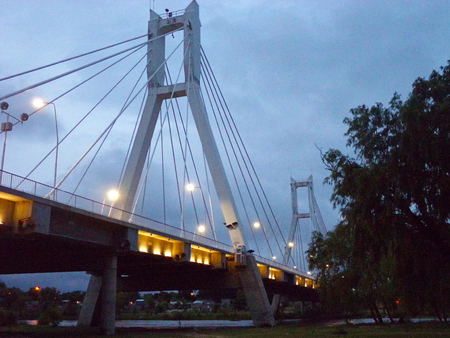 Column of a bridge over the river with artificial lighting and thick steel cables
