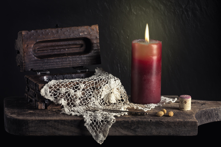 still life with candle , copper wooden table and wine