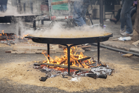 valencian: Valencian paella cooking on log fire in local Spainish village Stock Photo