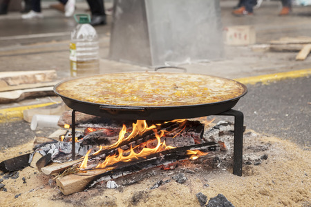 log fire: Valencian paella cooking on log fire in local Spainish village Stock Photo