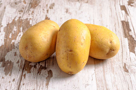 three raw potatoes on board Reklamní fotografie