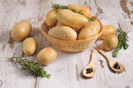 potatoes on wicker basket and rosemary leaves