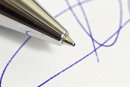 underwrite: signing with pen on a white background