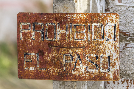 rusty iron sign with the legend of trespassing photo