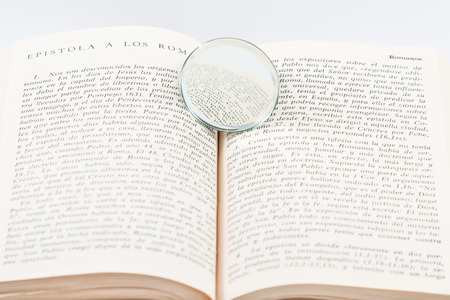 lexicon: magnifying glass over top open book on white background Stock Photo