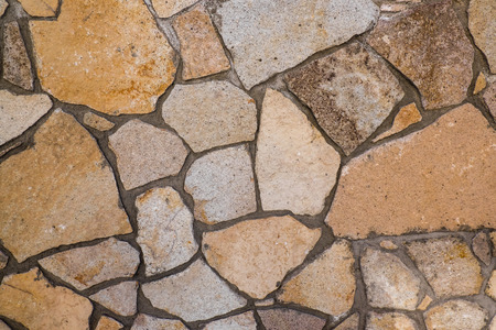 cobblestone street: Background of a wall orange granite stone bearing