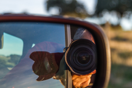 self-portrait of a photographer in a mirror of a car day Stock Photo