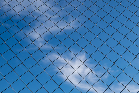 iron fence: iron fence on a blue sky with small clouds