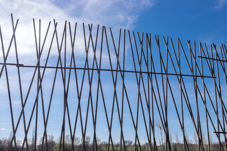 bearded wires: iron fence on a blue sky with small clouds