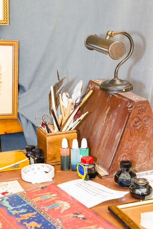 manuscripts: antique desk with jars of ink, pens and lamp for manuscripts Stock Photo