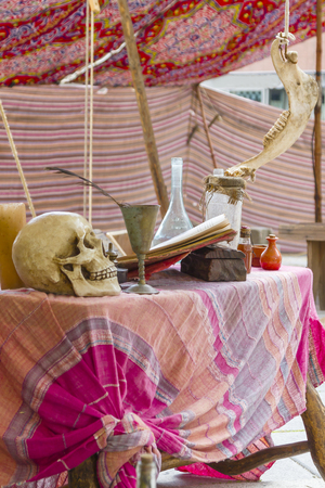 witchcraft: table with potions, books and skull of medieval times, witchcraft and medicine.