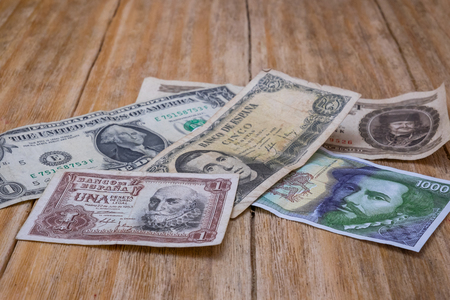us paper currency: several bills Spanish pesetas, US dollar and Hungarian forint over a wooden table