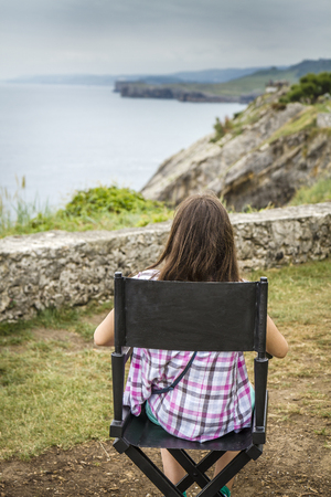 director's chair: Teenage girl resting quietly and watching the sea in the directors chair film after a walk along the coast