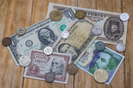 us paper currency: several notes and coins Spanish pesetas, US dollar and Hungarian forint over a wooden table