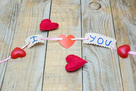 """parejas romanticas: cable de color rosa la celebraci�n de varias piezas de cart�n con las palabras """"te amo"""" Foto de archivo"""