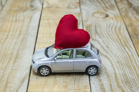 car with a red heart on the roof carrying love Stock Photo