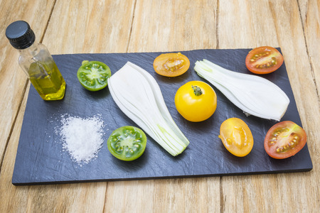 yellows: red tomatoes, yellows, greens and spring onions with salt and oil shale above a tray on a wooden table