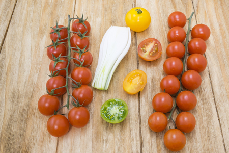 yellows: red tomatoes, yellows, greens and spring onions on a wooden table