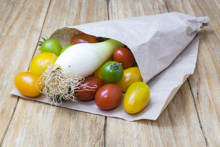 yellows: red tomatoes, yellows, greens and scallions in a paper cone on a wooden table Stock Photo