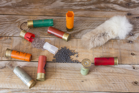 sober: set hunting shotgun cartridges and a tail rabbit sober a wooden table Stock Photo