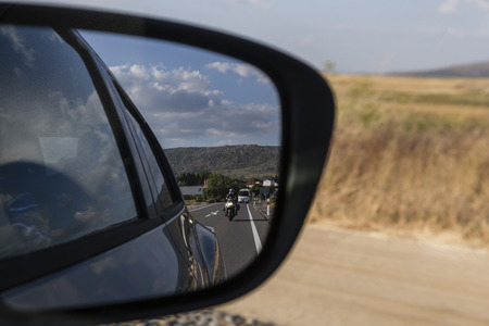 overtaking: reflections in the mirror of a car conduccido by day