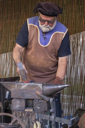 medieval blacksmith: Avila, Spain - September 03, 2016 exhibition of a blacksmith in a medieval market Editorial