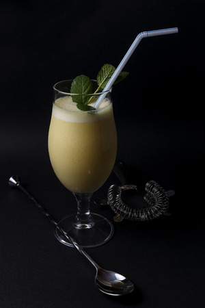 Cocktail of pineapple colada with mint next to cocktail accessories on a black background Stock Photo
