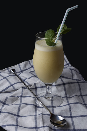 colada: Cocktail of pineapple colada with mint next to cocktail accessories on a cloth and the black background Stock Photo
