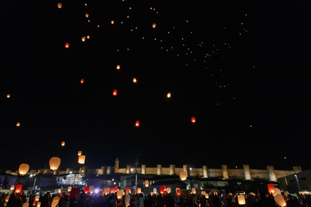 Sky lanterns flying above the city walls of Avila