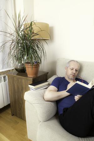 living room wall: Man with glasses reading a book on a sofa next to some green plants