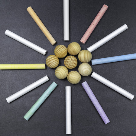 chalks: Black chalkboard with colored chalks forming a circle and wooden balls in the center Stock Photo
