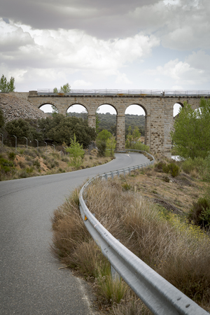 Road passing through the eyes of an old stone bridge for the railway
