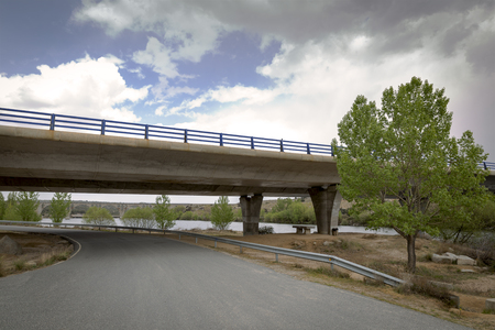 Road passing under a bridge of a motorway next to a dam and an old railway bridge