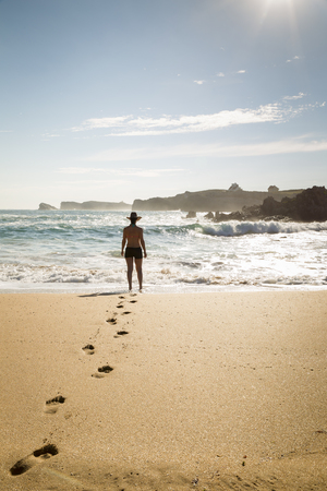 woman walking through the sand of a lonely and beautiful beach Stok Fotoğraf