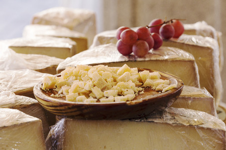 serving of cheese in pieces served on a round wood in a traditional market