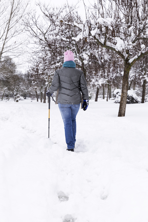 woman walking and having fun in a snowy park on a cold winter day