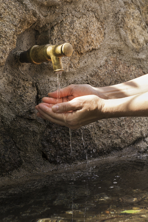 womans hands picking fresh water from the spout of a stone fountain
